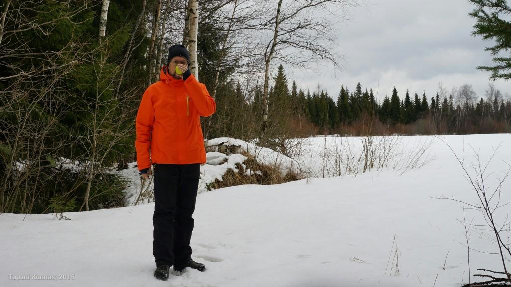 Iltapäiväkahvit metsän siimeksessä. Taustalla heinäpelto uinuu vielä lumivaipan alla.