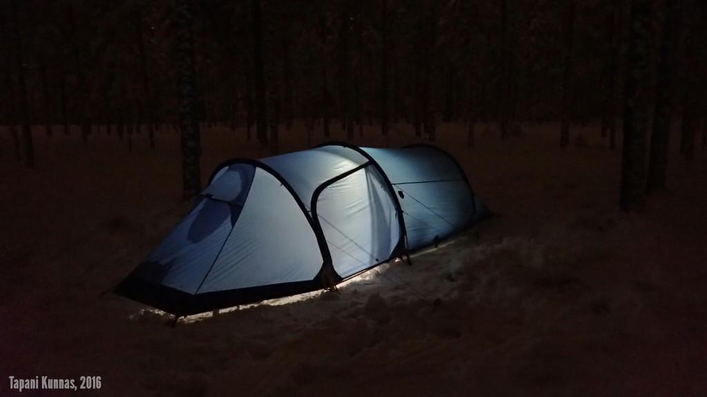 Erämaakaksio tunnelmavalaistuksessa, joka syntyy paristokäyttöisellä telttalyhdyllä.
