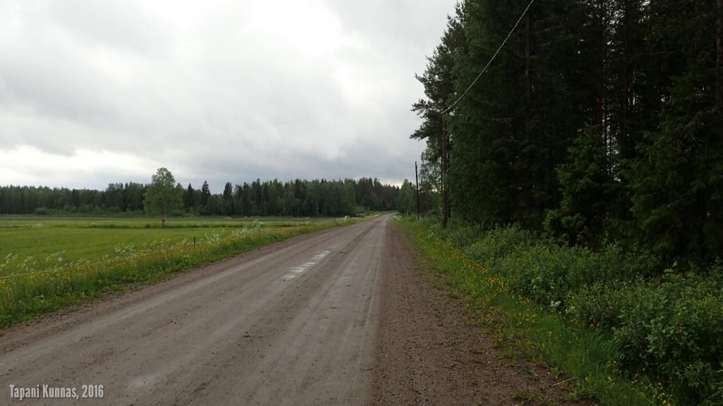 Sadepilvet roikkuvat matalalla soratiemaiseman yllä, kun lähden puoliltapäivin polkemaan kohti Kajaania.