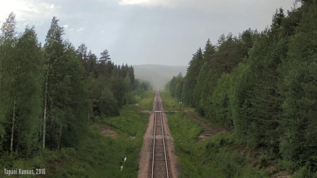 Sadekuuro Lahnaslammen kaivokselle vievän rautatien yllä.