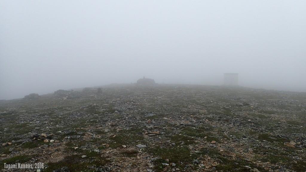 Láŋkán huipun kivimuuri ja muuntajakoppi pilvessä. TV-masto on jossain noiden takana.