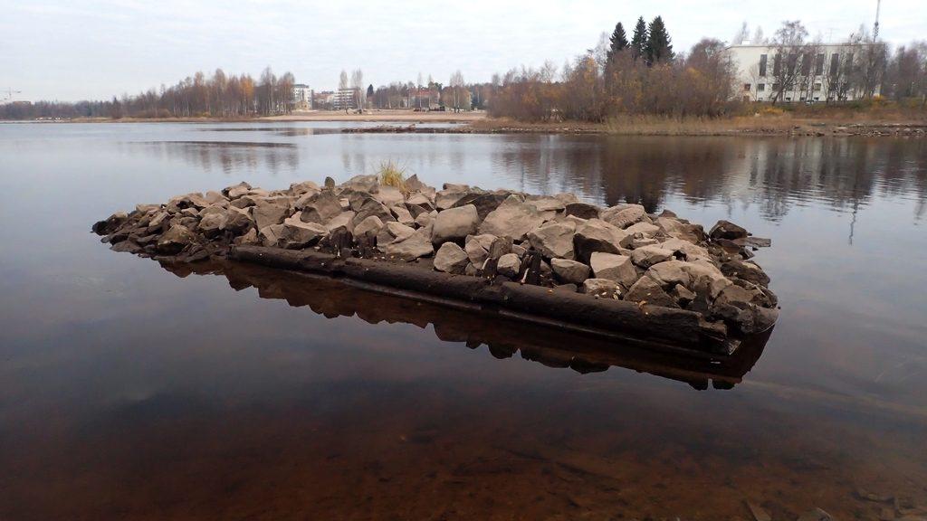 Jos vesi on normaalikorkeudella, näkyy tässä vain kivinen saari. Veden alta esiin tulleet puurakenteet paljastavat, että tässä on vanha kiviarkku, joka lienee peräisin ajalta, jolloin Oulujoessa uitettiin puuta.