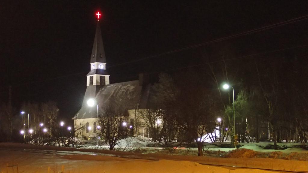 Rovaniemen kirkko. Erikoista, että risti on valaistu punaiseksi.